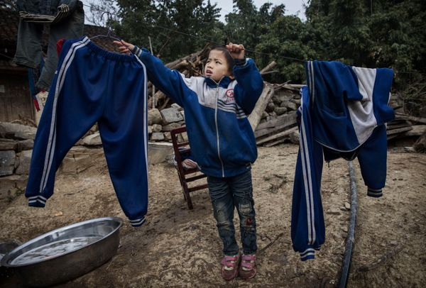 Luo Hongniu, 8, hangs laundry after washing clothes with her siblings.