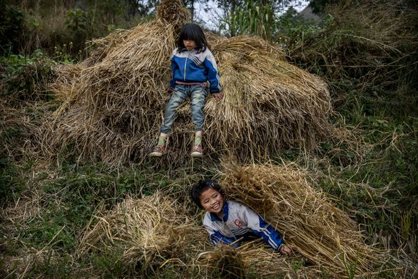 Luo Hongni, 11, top and sister Luo Hongniu, 8, play in hay bales.