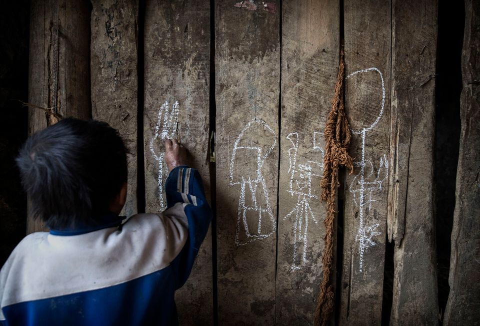 Luo Lie, 5, uses chalk to draw a picture on a wooden door of the family home. In the case of the Luo grandparents, who are el