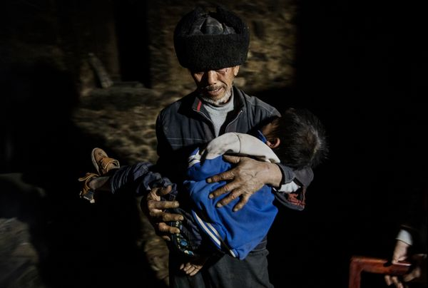 Grandfather Luo Yingtao, 64, carries his grandson Luo Lie, 5, to bed at the family house.
