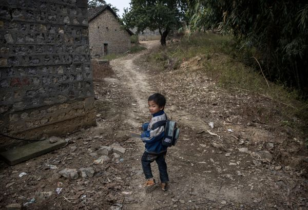Luo Lie, 5, walks home from school. China's government says it is making child welfare a national priority, and will work to