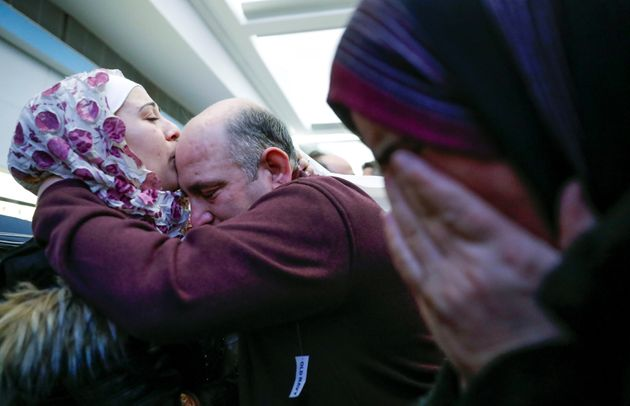 Syrian refugee Baraa Haj Khalaf kisses her father Khaled as her mother Fattoum cries after arriving at...