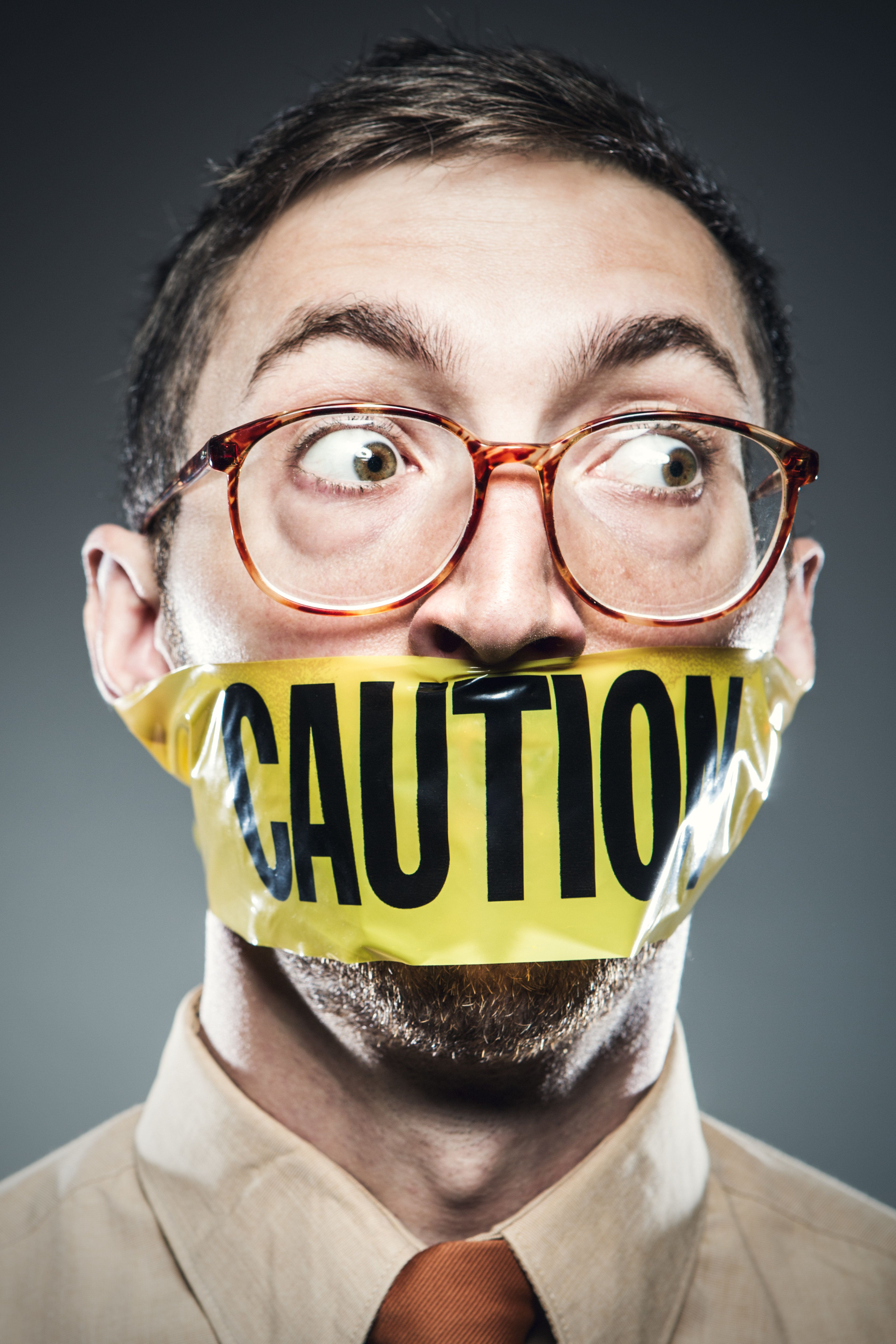 A man has yellow Caution tape wrapped over his mouth, preventing him from speaking his thoughts or ideas.  Concept on freedom of speech and censoring of opinions.