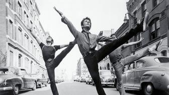 (Original Caption) New York, New York: Evolution Or Revolution. George Chakiris leads some dancers down a New York street in a scene from West Side Story. The musical version of Romeo and Juliet, boasted, among other things, spectacular dancing.