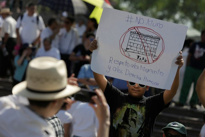 "A demonstrator holds a placard reading: ""No wall. Respect to immigrants and human rights"" during a protest against President"
