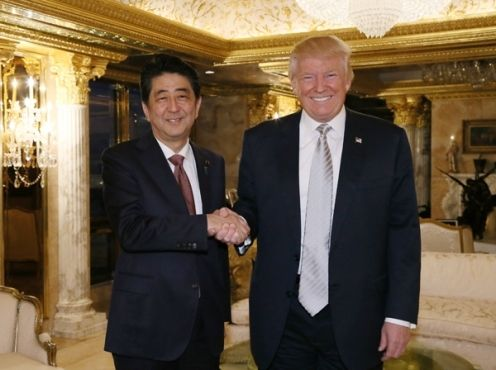 Prime Minister of Japan Shinzō Abe shakes hands with Donald Trump.