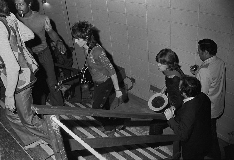 The Rolling Stones take the stage in 1969; Schneider is seen holding railing next to Mick Jagger.