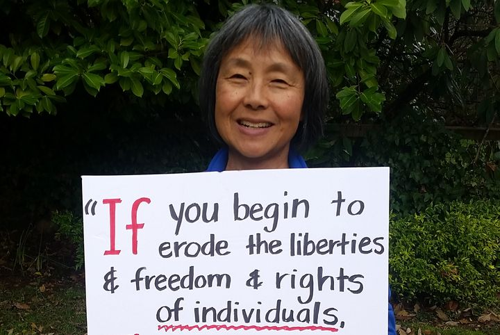 Barbara Yasui holds a sign featuring a quote from her uncle, civil liberties activist Minoru Yasui, on Jan. 21, 2017. The ent