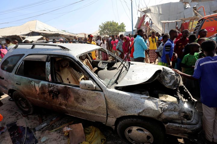 Civilians stand near a car destroyed in a suicide bomb explosion at the Wadajir market in Madina district of Somalia's capita
