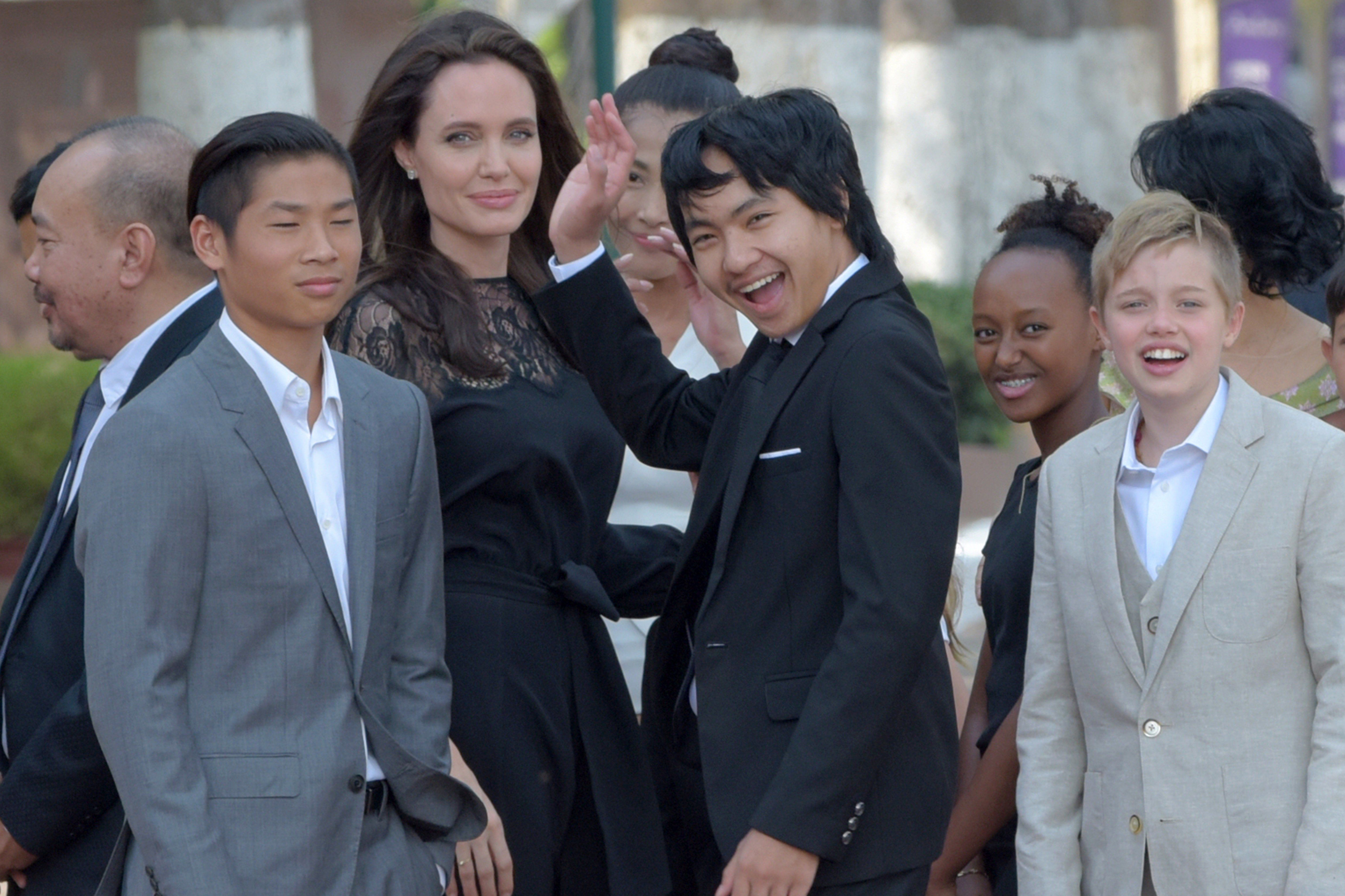 Angelina Jolie and her children gesture to media in front of the royal residence for a meeting with Cambodian King Noro