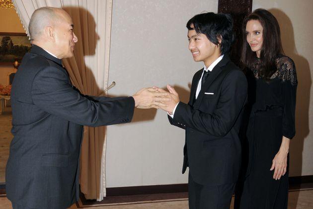 Maddox Jolie-Pitt greets Cambodian King Norodom Sihamoni as Angelina Jolie looks on at the royal residence...