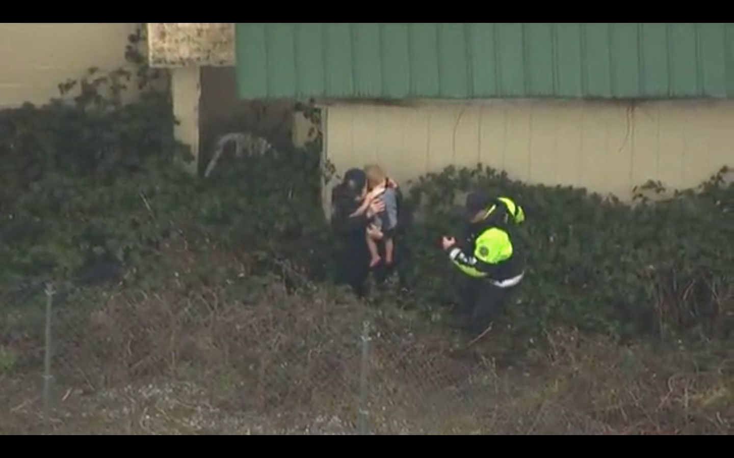 Two officers are seen recovering a 2-year-old child from some bushes after the child went missing from his Portland, Oregon h
