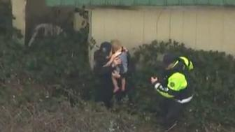 Two officers are seen recovering a 2-year-old child from some bushes after he went missing from his Oregon home