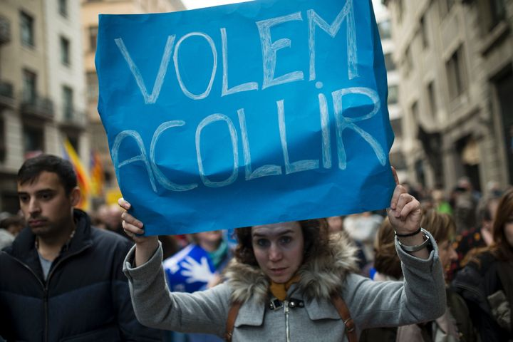 "A woman holds a placard reading ""We want to welcome"" during a demonstration to demand to welcome refugees in Barcelona."