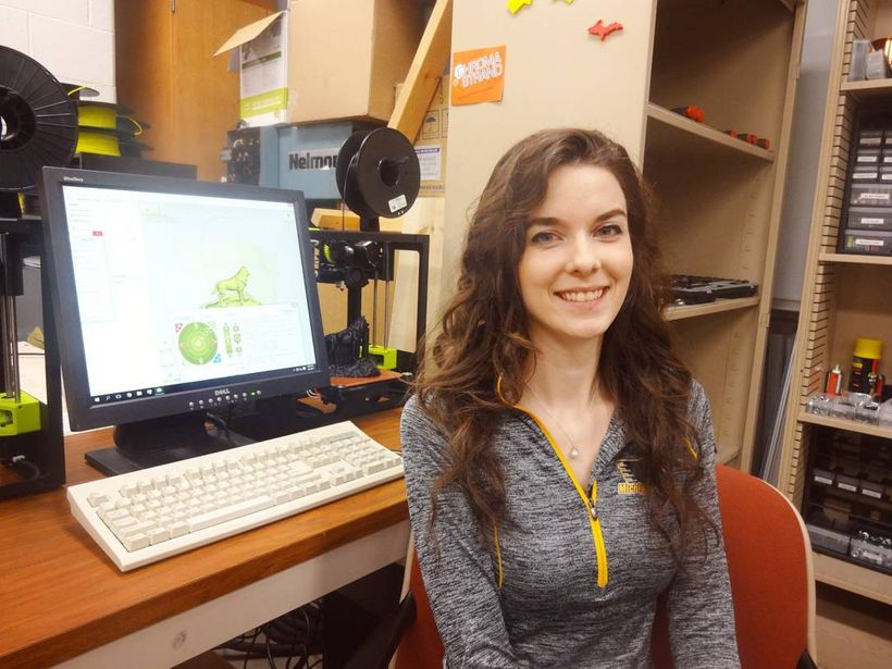 Emily Petersen, a co-author on the study, in a lab with open source Lulzbot Mini 3-D printers being used to print husky statu
