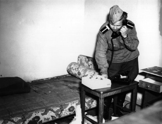 A Russian soldier using Eva Braun's phone in her bedroom in Hitler's shelter on 6 July