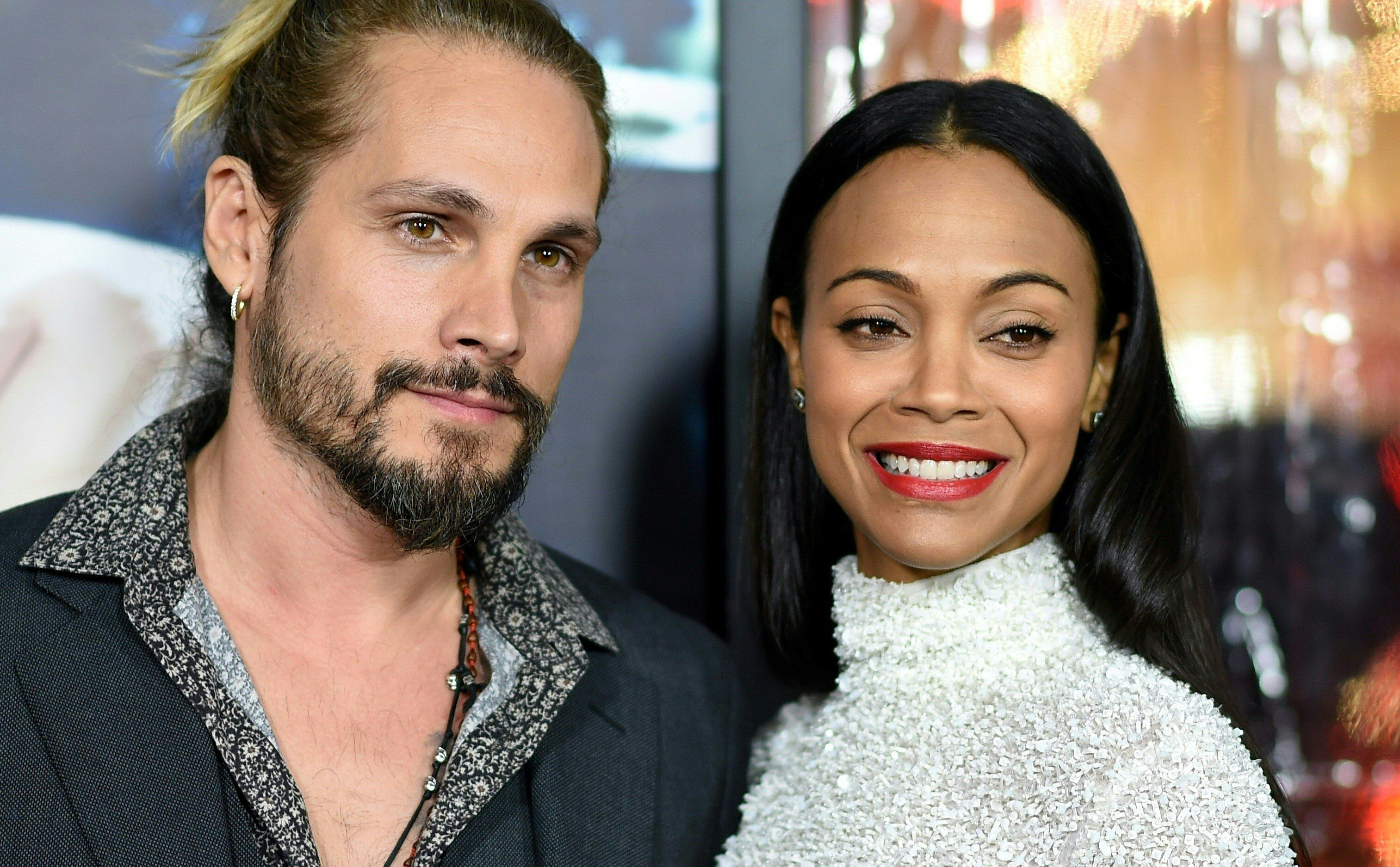 Artist Marco Perego and actress Zoe Saldana arrive for the  for the world premiere of Warner Bros. 'Live By Night,' January 9, 2017 at the TCL Chinese Theater in Hollywood, California. / AFP / Robyn Beck        (Photo credit should read ROBYN BECK/AFP/Getty Images)