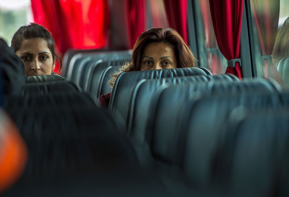Kurdish Iraqi women leave aboard a bus the 'Jungle' migrant camp in Calais, northern France, on October 12, 2016, for a recep