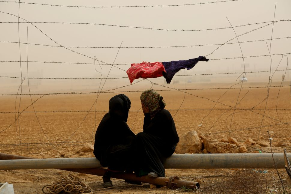 Syrian women sit next to the fence during a sandstorm at a temporary refugee camp in the village of Ain Issa, housing people
