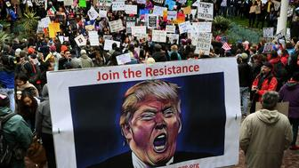 Protesters carry anti-Trump signs during a 'Not My President Day' demonstration outside City Hall in Los Angeles, California, on February 20, 2017. / AFP / Mark RALSTON        (Photo credit should read MARK RALSTON/AFP/Getty Images)