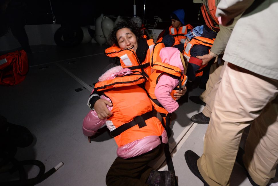 Syrians woman holds her children after 50 refugees captured by Turkish coast guard while they were illegally trying to reach