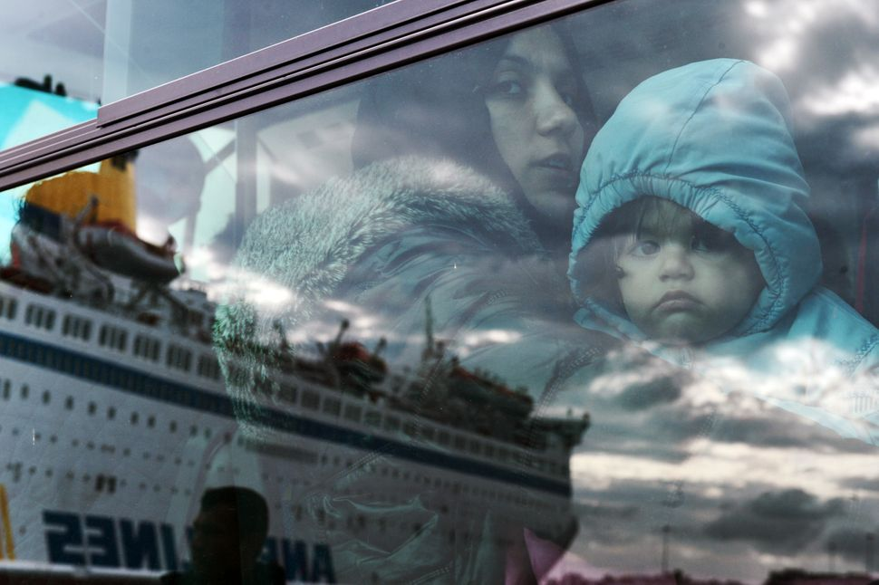 A woman and a child peer from a bus, after migrants and refugees disembarked from a government chartered ferry, seen in refle