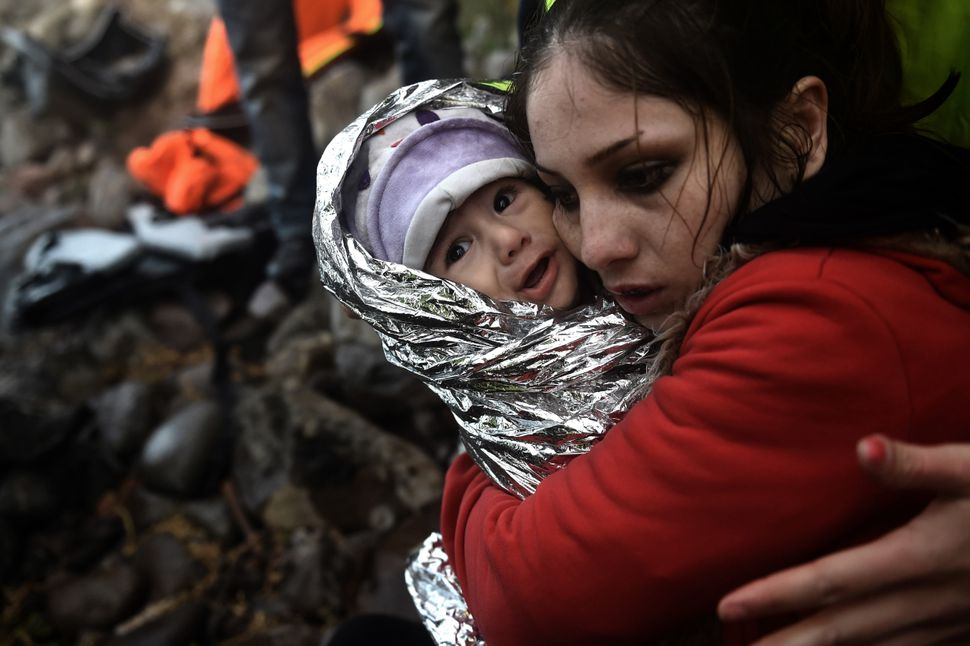 A woman hugs a baby wrapped in an emergency blanket as refugees and migrants arrive on the Greek island of Lesbos after cross