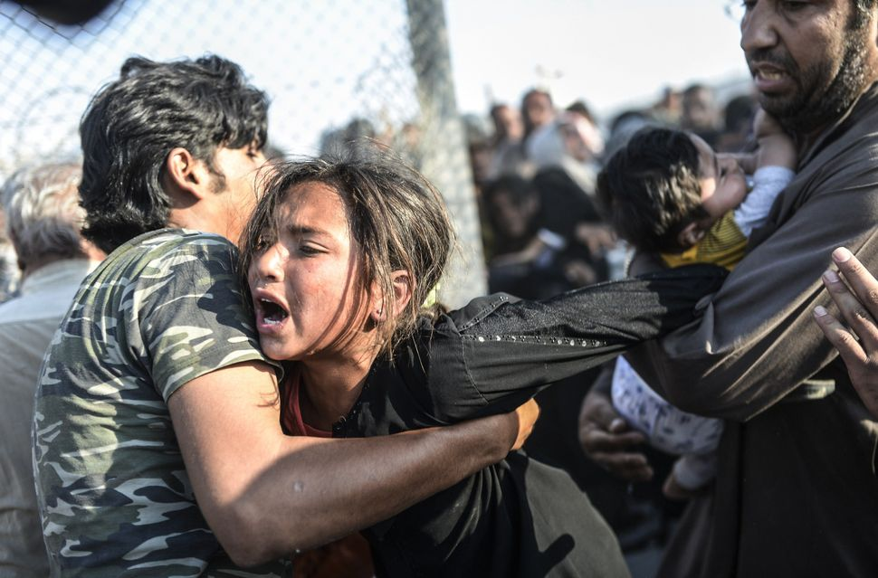 Syrians fleeing the war rush through broken down border fences to enter Turkish territory illegally, near the Turkish border
