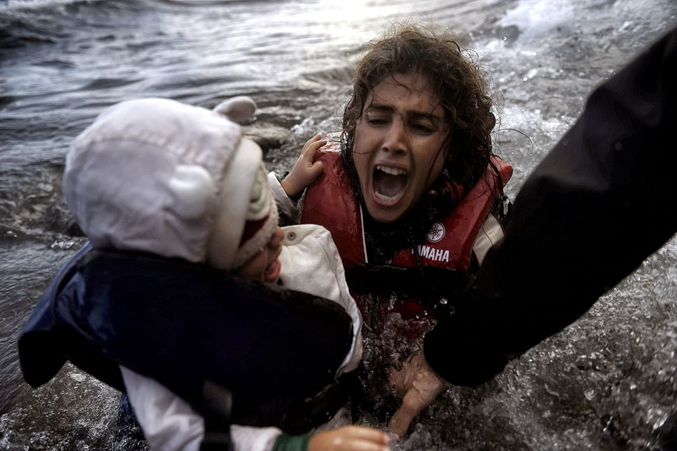A woman falls into the water with her child as they disembark off a dinghi as refugees and migrants arrive at the Greek islan