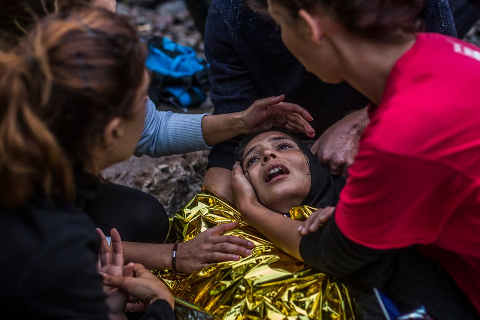 A woman reacts as she arrived with other refugees on the shores of the Greek island of Lesbos after crossing the Aegean sea f