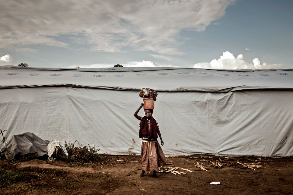 A Burundian woman carries laundry at the Gashora refugee camp in Gashora, Bugesera, Rwanda Wednesday April 29, 2015.