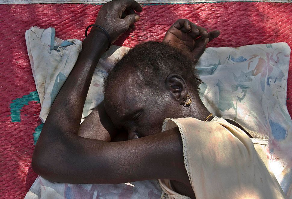 A South Sudanese woman sleeps on January 7, 2014 at the Ochaya Rhino refugee camp in the Arua District, about 495 kilometres
