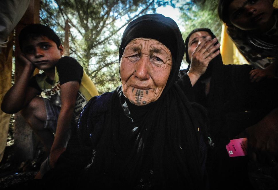 An 80 year old women becomes overwhelmed by the trauma of walking for 2 days from Qaraqosh is waiting to receive medical atte