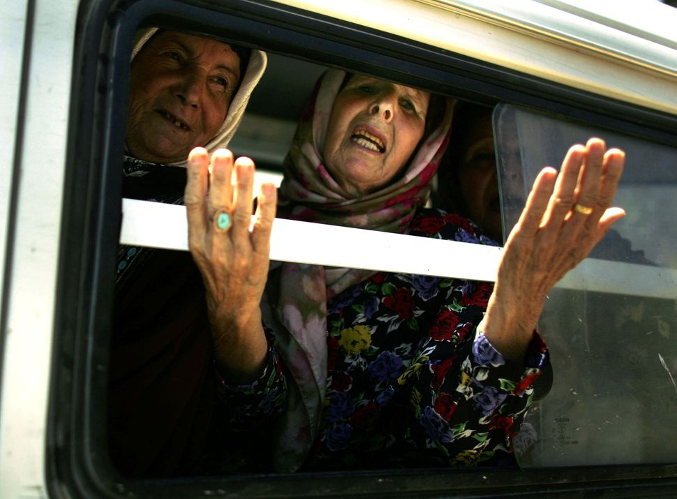 A woman gestures from a van carrying displaced people, one of thousands of civilians fleeing their southern villages as a for