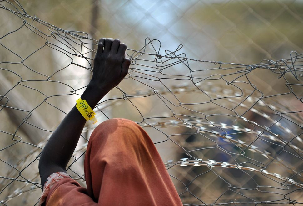 A newly registered Somali refugee supports herself on a chain-link perimeter fence outside a registration and medical aid fac