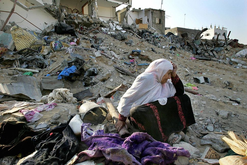 A Palestinian woman breaks down in tears trying to salvage usable belongings from her demolished house in the northern Gaza S