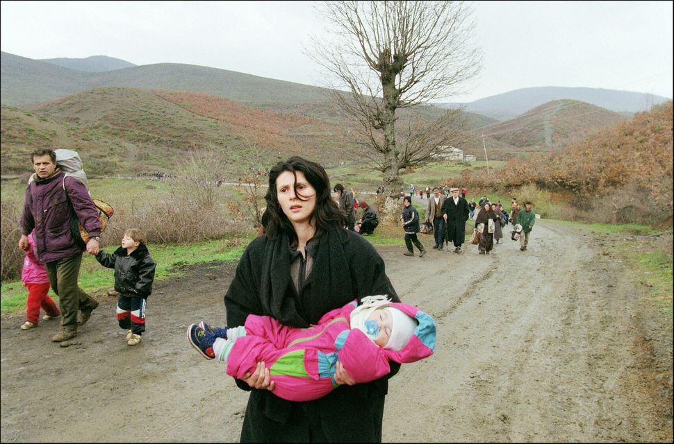 A woman carrying a baby arrives in Albania on April 3, 1999 with fellow ethnic Albanian refugees fleeing Serb repression in K