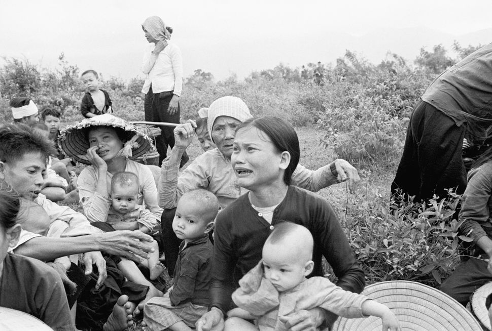 Weeping South Vietnamese villagers huddle together as they await evacuation to new homes following battle near here recently