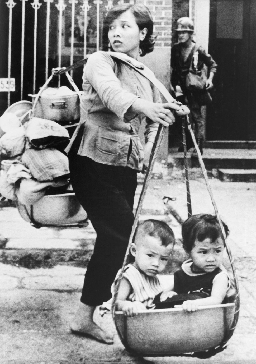 Vietnamese woman carries her children and possessions on bamboo pole as she tries to escape fierce fighting in the Cholon sub