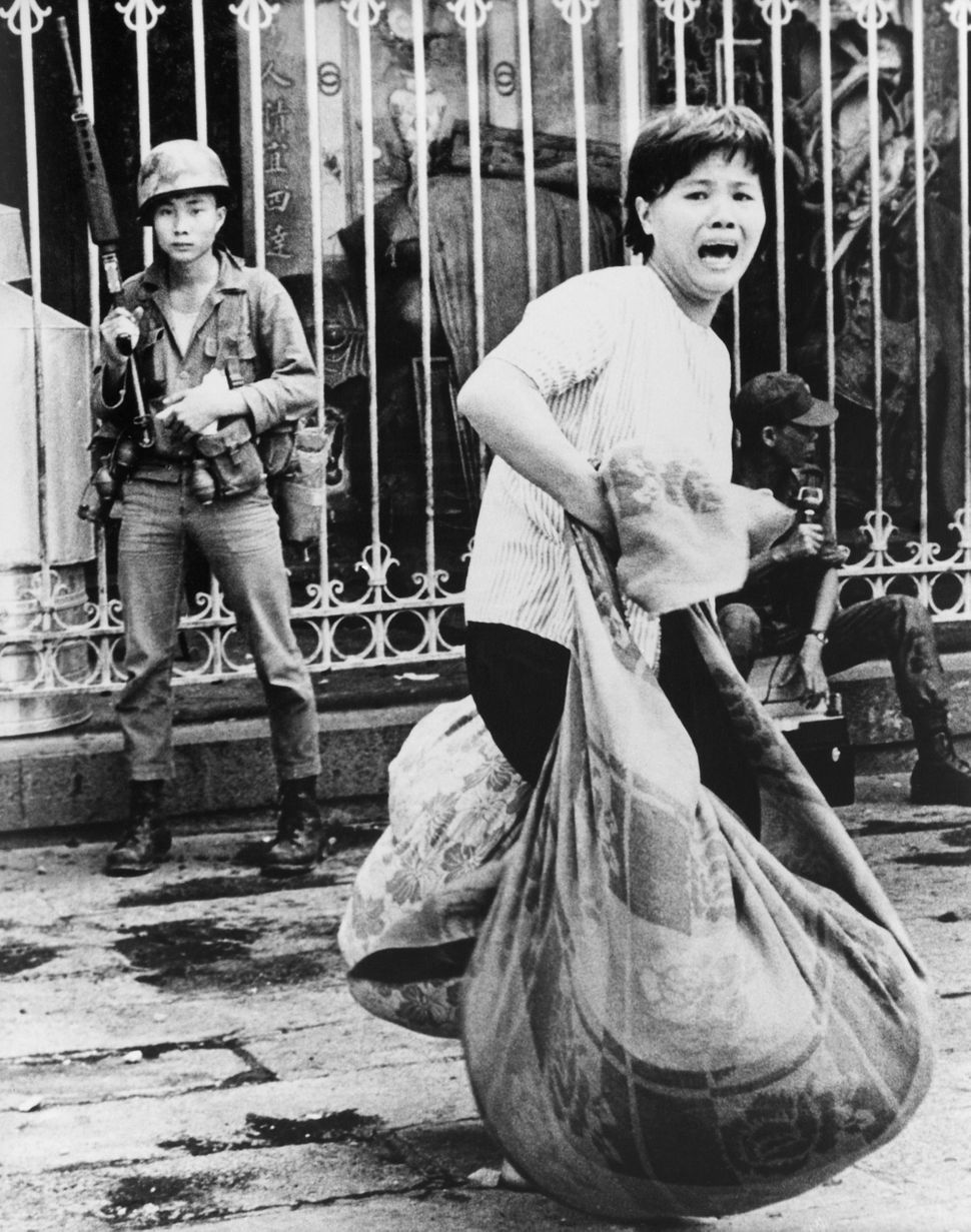Screaming refugee woman flees her home with bundled possessions during Viet Cong attack on Saigon's Chinatown during the Mini