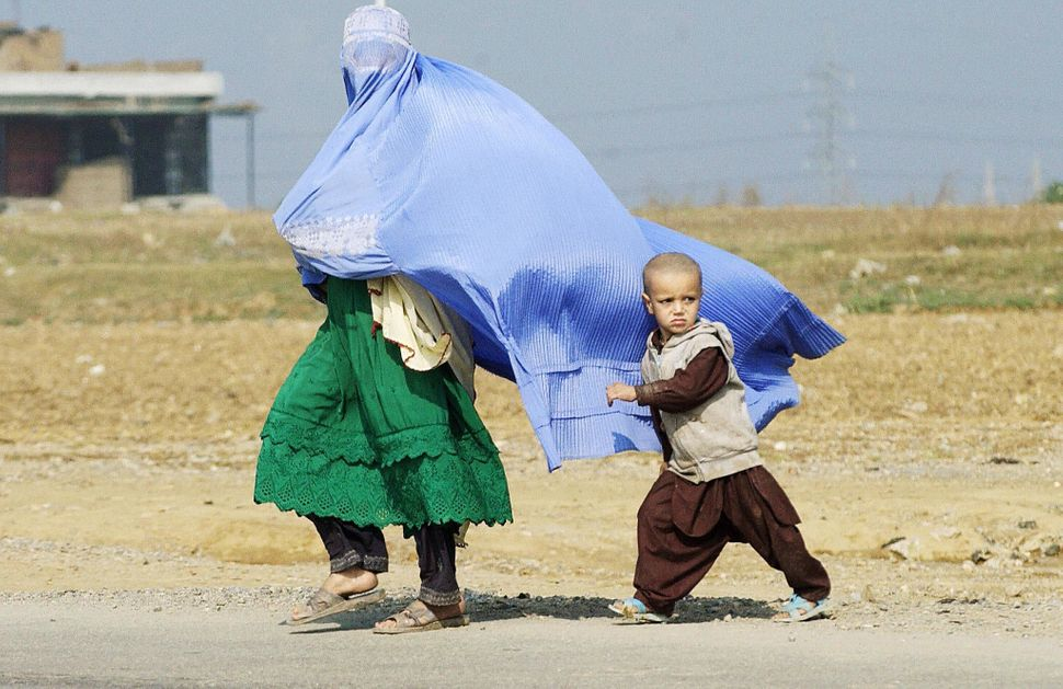 An Afghan refugee woman dressed in a burqa and her child cross a road on their way to their home in a refugee camp in the out