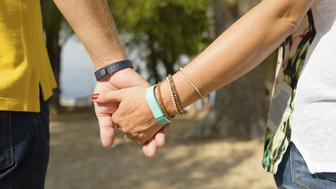 A mid-adult couple wearing fitness activity tracking devices, holding hands, enjoying the outdoors.