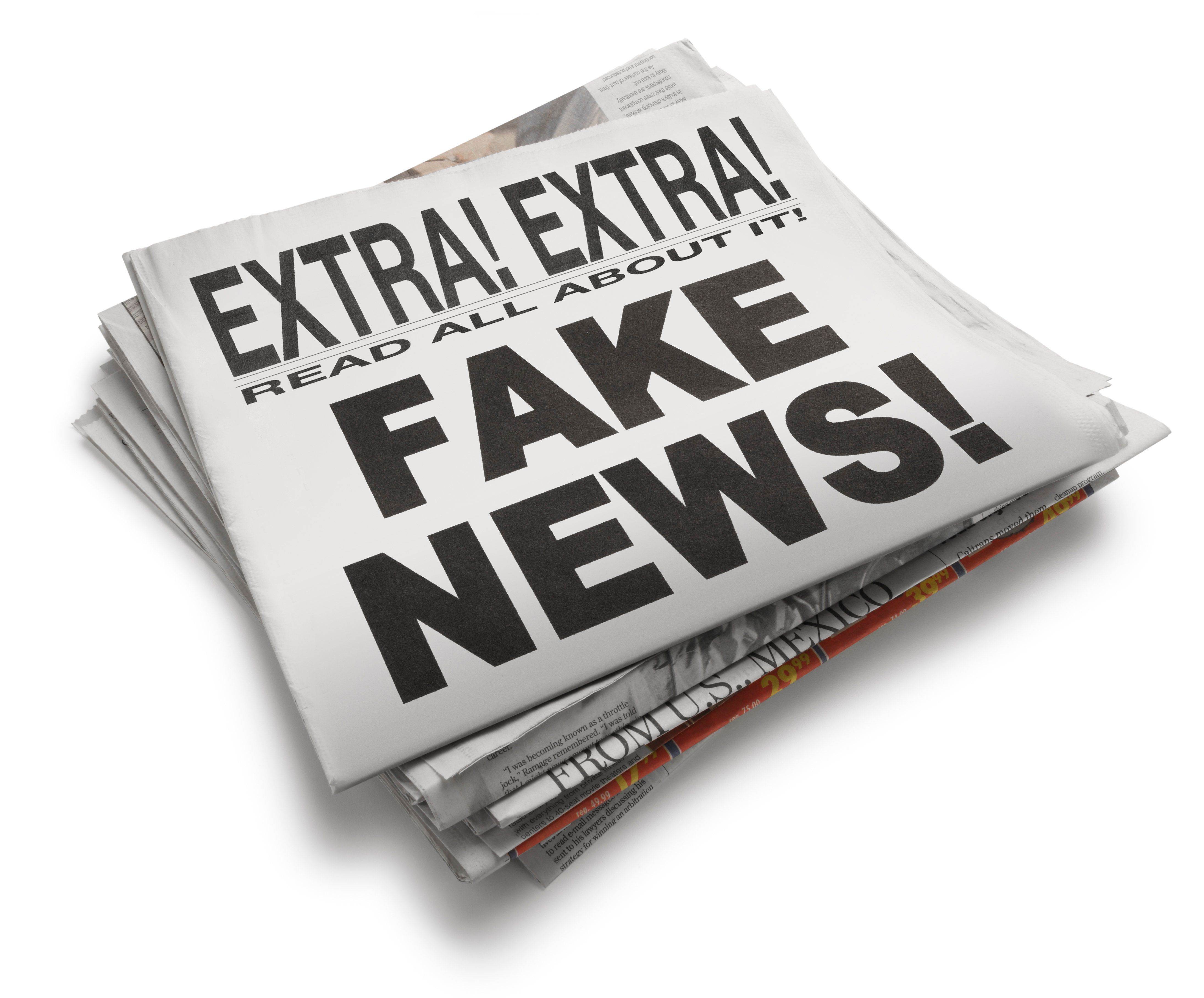 The front page of a newspaper with the headline 'Fake News' which illustrates the current phenomena. Front section of newspaper is on top of loosely stacked remainder of newspaper. All visible text is authored by the photographer. Photographed in a studio setting on a white background with a slight wide angle lens.