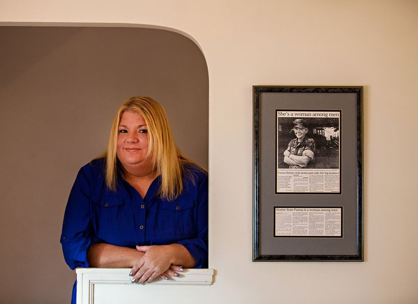 Rosie Palfy stands in an alcove in her old home next to a framed article from the <em>Plain Dealer</em> (Cleveland) in 1993 a