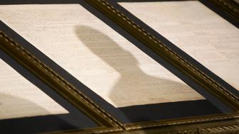 The shadow of U.S. President Barack Obama is seen on the Constitution of the United States while speaking about America's national security at the National Archives in Washington, May 21, 2009.   REUTERS/Larry Downing (UNITED STATES POLITICS)