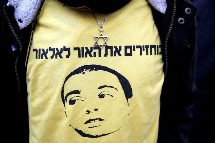"A supporter of Elor Azaria wears a shirt with the words in Hebrew ""Bringing the light back to Elor"" during a protest outside"