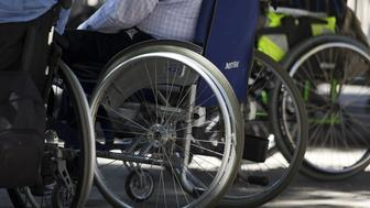 Disabled individuals in wheelchairs take part in a demonstration to demand more accessibility options for disabled people near the French National Assembly in Paris on July 6, 2015. AFP PHOTO / KENZO TRIBOUILLARD        (Photo credit should read KENZO TRIBOUILLARD/AFP/Getty Images)