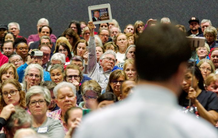 Unhappy constituents hold up signs duringRep. Scott Taylor's town hall meeting at Kempsville High School in Virginia Be