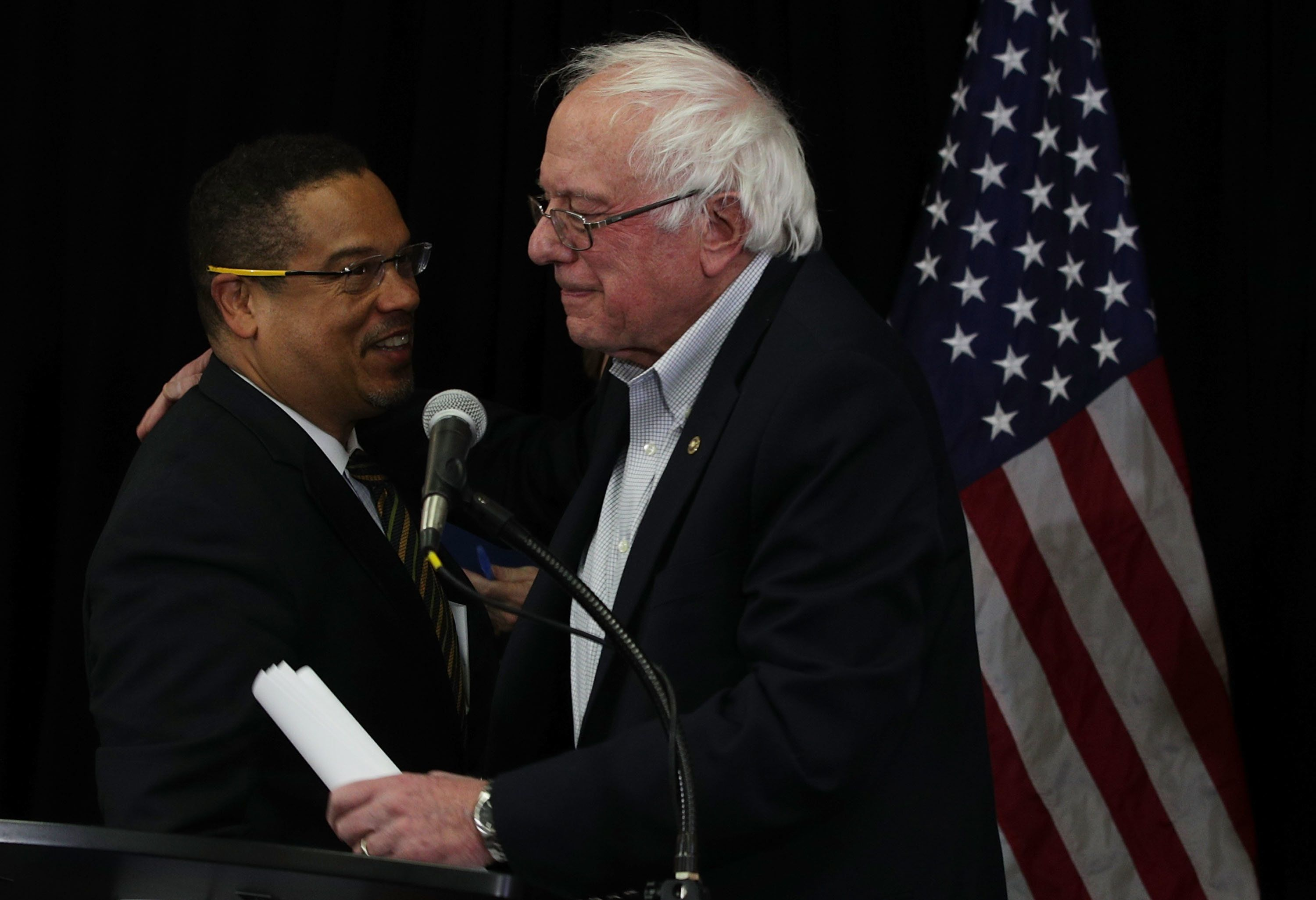 Rep. Keith Ellison (D-Minn.), left, and Sen. Bernie Sanders (I-Vt.) embrace during an event at the headquarters of American F