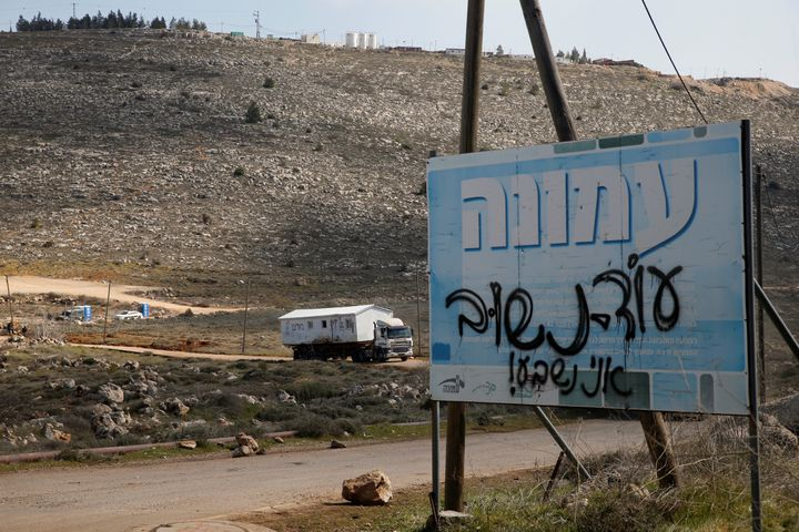 "A sign covered in text reading, ""we will return, I swear,"" marks the road leading to an illegal Israeli outpost of Amona"